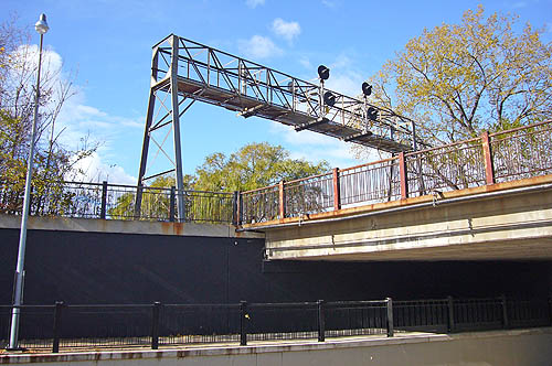 Truss holds up warning lights across a metal bridge, while underneath runs an underpass with flat black walls