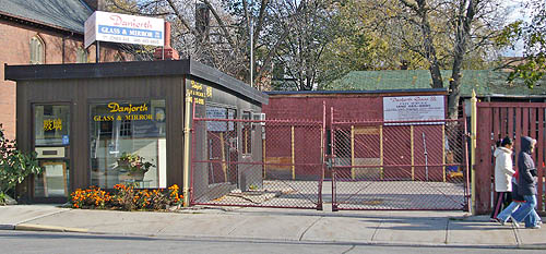 Squat rectangular building, almost a single room, is labelled Danforth Glass & Mirror and sits on a fenced-in paved yard