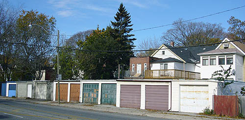 Garages with chipped paint in rust, green, purple, and white lead to a few two-storey houses