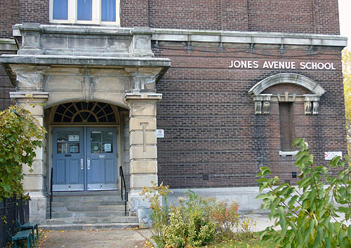 Brickbuilding is labelled JONES AVENUE SCHOOL and has masive stone portico