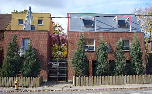 Three-storey buildings in red brick, with porthole windows and roofs in yellow and blue