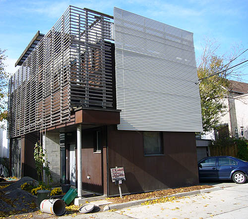 Three-floor house is covered by screens made of metal slats. One screen wraps around a two-storey side balcony