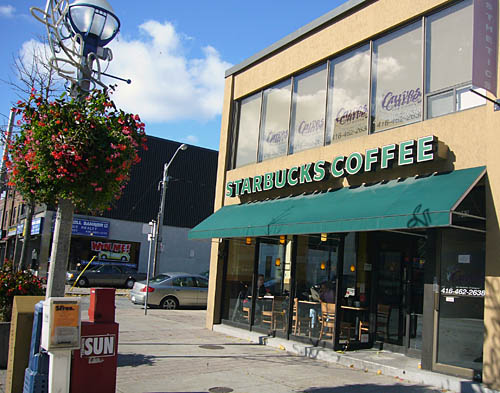 Green awning on tawny stucco building sits below a sign: STARBUCKS COFFEE