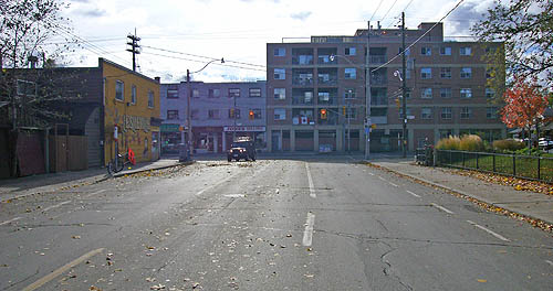 Four-lane street littered with autumn leaves terminates at a bank of three-storey buildings