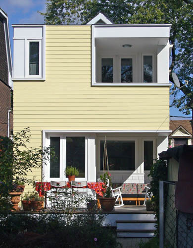 Flat wall in yellow siding has upper recessed upper deck in white trim, a lower deck in white trim, and a white-surrounded narrow window at top left