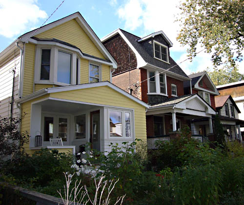 Butter-yellow house is two storeys tall, has a white-trimmed front deck with no corner column, and sits alongside brown-brick neighbours