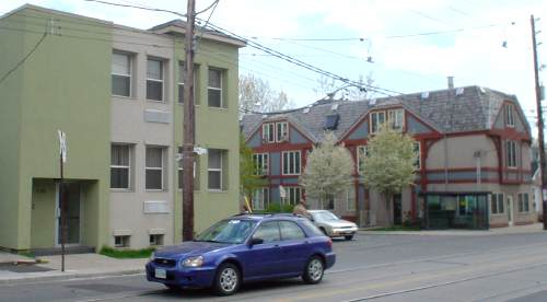 T-intersection shows green-and-cream stucco building on near corner and blue-and-burgundy mock-Tudor building on far corner