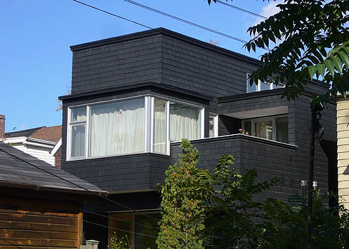 Black-shingled house has glass-windowed solarium alongside an open deck with a quarter-roof at its rear