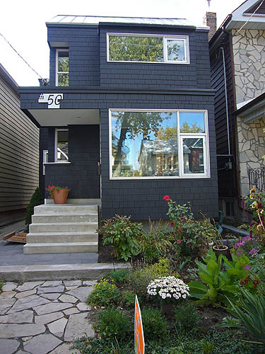 Black-shingled house with colour ful garden, inset side windows, and short concrete staircase