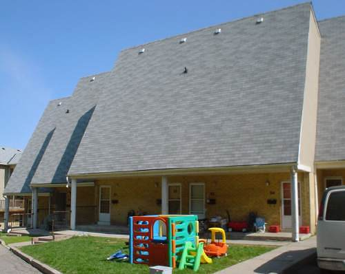 Three north-facing windowless roofs, each set back from the other. Children's play sets sit on trapezoidal lawn area
