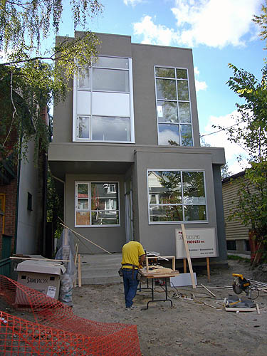 Grey-stucco house has giant windows and protruding rectangular volumes. A workman in a yellow T-shirt tends to a machine on the unfinished front yard