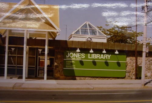Stone building with giant green sign reading JONES LIBRARY and yellow canopy over entrance